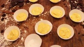 A mão fêmea põe a massa crua para queques no bakeware de papel video estoque