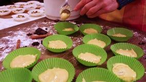 A mão fêmea põe a massa crua para queques no bakeware de papel vídeos de arquivo
