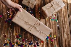 A mão fêmea pegara um presente envolvido no papel do ofício fotografia de stock royalty free