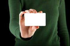 A mão fêmea prende um cartão branco em branco foto de stock