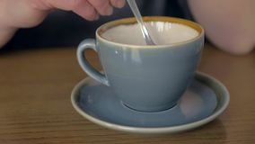Mão fêmea que agita o café em um copo vídeos de arquivo