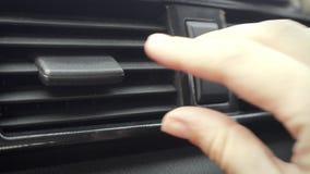 Mão fêmea que ajusta o sentido da aleta do condicionamento de ar no carro video estoque
