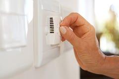 Mão fêmea que ajusta a temperatura com o seletor no condicionamento de ar foto de stock