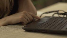 Mão fêmea que datilografa no caderno do teclado para escrever acima a letra pelo fim do email filme