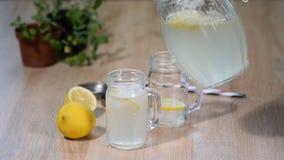 Mão fêmea que derrama a limonada caseiro no frasco vídeos de arquivo