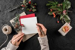 Mão fêmea que escreve uma letra a Santa no fundo escuro com presente do Natal, bagas, ramos do abeto, skein da juta Xmas imagens de stock royalty free