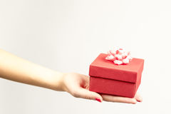 Mão fêmea que guarda a caixa de presente vermelha com uma curva isolada no fundo branco Imagens de Stock Royalty Free