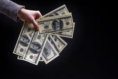 Mão fêmea que guarda cem notas de dólar no fundo preto C Foto de Stock Royalty Free