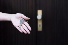 Mão fêmea que guarda chaves da casa Imagens de Stock