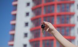 Mão fêmea que guarda chaves no fundo da casa nova Conceito 6 dos bens imobiliários Chaves ao apartamento novo Casa ou aluguer mov Fotografia de Stock Royalty Free