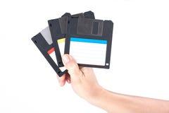 Mão fêmea que guarda disquetes foto de stock