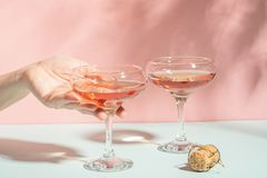 Mão fêmea que guarda elegantemente um vidro do fundo delicado do rosa do champanhe ou do vinho da luz solar brilhante Minimalismo fotos de stock royalty free