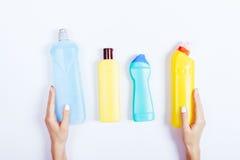 Mão fêmea que guarda garrafas azuis e amarelas do detergente em um wh Imagem de Stock