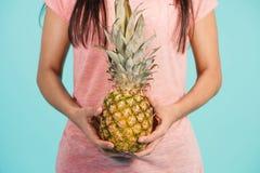 Mão fêmea que guarda o abacaxi maduro Foto de Stock Royalty Free