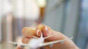 Mão fêmea que guarda o avião do brinquedo, espaço da cópia para o texto Passageiro com o avião modelo pequeno no aeroporto Movime vídeos de arquivo
