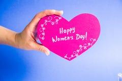 Mão fêmea que guarda o coração de papel cor-de-rosa no fundo azul - dia feliz do ` s das mulheres Foto de Stock Royalty Free