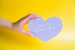 Mão fêmea que guarda o coração de papel cor-de-rosa no fundo dourado - dia feliz do ` s das mulheres Imagens de Stock
