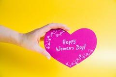 Mão fêmea que guarda o coração de papel cor-de-rosa no fundo dourado - dia feliz do ` s das mulheres Foto de Stock Royalty Free