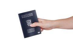 Mão fêmea que guarda o passaporte croata fotografia de stock