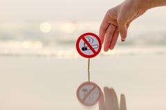 Mão fêmea que guarda o sinal não fumadores na praia foto de stock