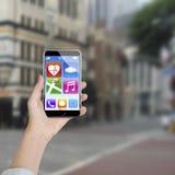 Mão fêmea que guarda o smartphone com ícones do app Fotografia de Stock Royalty Free