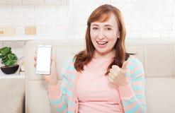 Mão fêmea que guarda o telefone branco no fundo branco do interior do trajeto de grampeamento em casa Mulher da Idade Média Copie Fotografia de Stock