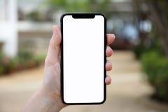 Mão fêmea que guarda o telefone com a tela isolada no backgro da natureza Fotografia de Stock Royalty Free