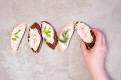 Mão fêmea que guarda a parte de pão de centeio com pasta salmon fotografia de stock
