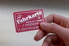 mão fêmea que guarda um bilhete para um passeio do carnaval com texto alemão: bilhete, válido para 1 passeio, 1 pessoa, nenhum ca imagem de stock royalty free