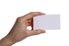 Mão fêmea que guarda um cartão vazio, isolado no fundo branco imagem de stock