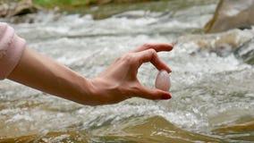 Mão fêmea que guarda um ovo do yoni do cristal de quartzo cor-de-rosa no fundo do rio A saúde das mulheres, unidade com conceitos filme