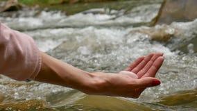 Mão fêmea que guarda um ovo do yoni do cristal de quartzo cor-de-rosa no fundo do rio A saúde das mulheres, unidade com conceitos video estoque