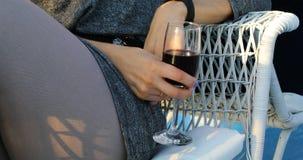 Mão fêmea que guarda um vidro do vinho tinto video estoque