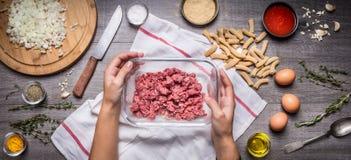 Mão fêmea que guarda uma bacia com carne triturada na mesa de cozinha rústica, em torno dos ingredientes da mentira para uma mass Imagem de Stock Royalty Free