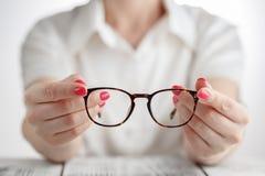 Mão fêmea que guarda vidros quadro um marrom Imagem de Stock