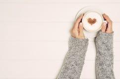 Mão fêmea que guarda a xícara de café na tabela, vista superior Fotografia de Stock Royalty Free
