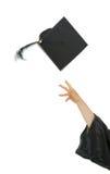 Mão fêmea que joga acima o tampão da graduação imagem de stock