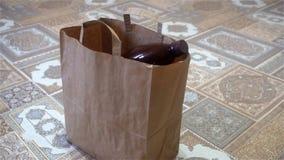 Mão fêmea que joga garrafas plásticas vazias em um saco de papel video estoque