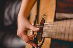 Mão fêmea que joga na guitarra acústica Fotografia de Stock Royalty Free