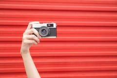 Mão fêmea que mantém a câmera do filme do vintage isolada no vermelho imagem de stock