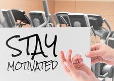 Mão fêmea que mantém o cartaz com estada do texto motivado no gym fotografia de stock royalty free