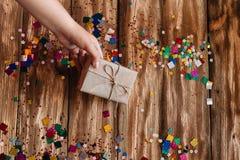 Mão fêmea que põe um presente envolvido sobre uma tabela de madeira fotografia de stock