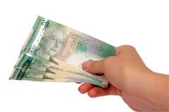 Mão fêmea que prende o dinheiro canadense imagem de stock