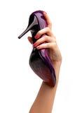 Mão fêmea que prende a sapata violeta Fotografia de Stock Royalty Free
