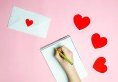 Mão fêmea que redige uma carta de amor Conceito do dia dos Valentim Cartão do Valentim do cumprimento Declaração do amor Convite  imagens de stock royalty free
