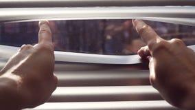 Mão fêmea que separa venezianas das venezianas com um dedo para ver completamente