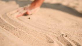 Mão fêmea que tira linhas calmas na areia branca na praia tropical da ilha em Tailândia 4K, Slowmotion video estoque
