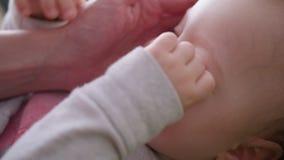 Mão fêmea que toca em um bebê que encontra-se na cama filme