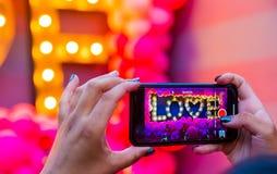 Mão fêmea que toma uma foto em seu telefone celular do amor da palavra foto de stock