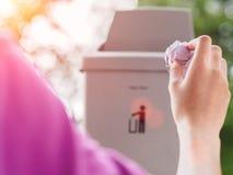Mão fêmea que trowing um papel em um escaninho de lixo no backgrou do bokeh Imagem de Stock